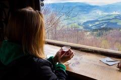 Η γυναίκα που κρατά ένα φλυτζάνι του τσαγιού, κορίτσι φαίνεται έξω το παράθυρο, η άποψη Στοκ φωτογραφίες με δικαίωμα ελεύθερης χρήσης
