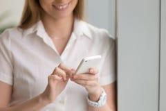 Η γυναίκα που κρατά το άσπρο τηλέφωνο, θηλυκά χέρια που χρησιμοποιεί το smartphone, κλείνει Στοκ Εικόνες