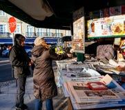 Η γυναίκα που λαμβάνει την αλλαγή στο περίπτερο Τύπου αγοράζει την εφημερίδα Στοκ Φωτογραφίες
