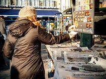 Η γυναίκα που λαμβάνει την αλλαγή στο περίπτερο Τύπου αγοράζει την εφημερίδα Στοκ φωτογραφία με δικαίωμα ελεύθερης χρήσης