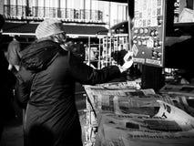Η γυναίκα που λαμβάνει την αλλαγή στο περίπτερο Τύπου αγοράζει την εφημερίδα Στοκ Εικόνα