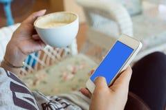 Η γυναίκα που πίνει τον καυτό καφέ στον καφέ και χρησιμοποιεί ένα κινητό τηλέφωνο Στοκ Εικόνα