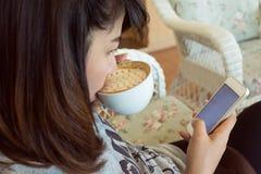 Η γυναίκα που πίνει τον καυτό καφέ στον καφέ και χρησιμοποιεί ένα κινητό τηλέφωνο Στοκ φωτογραφίες με δικαίωμα ελεύθερης χρήσης