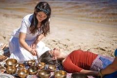 Η γυναίκα που παίζει ένα τραγούδι κυλά επίσης γνωστός ως θιβετιανά τραγουδώντας κύπελλα, κύπελλα Himalayan Παραγωγή του υγιούς μα Στοκ εικόνα με δικαίωμα ελεύθερης χρήσης