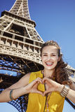 Η γυναίκα που παρουσιάζει καρδιά που διαμορφώνεται παραδίδει το μέτωπο του πύργου του Άιφελ, Παρίσι Στοκ Φωτογραφίες