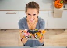 Η γυναίκα που παρουσιάζει πιάτο με το τέχνασμα ή μεταχειρίζεται την καραμέλα για το κόμμα αποκριών Στοκ εικόνες με δικαίωμα ελεύθερης χρήσης