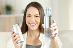 Η γυναίκα που παρουσιάζουν ένα μπουκάλι νερό και το α μπορούν Στοκ Εικόνες
