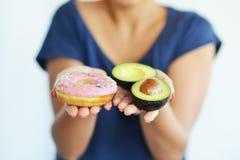 Η γυναίκα που προσφέρει δύο μισά του φρέσκου αβοκάντο και ένα ελκυστικό ρόδινο doughnut, επιλέγει υγιής ή νόστιμος στοκ εικόνες με δικαίωμα ελεύθερης χρήσης
