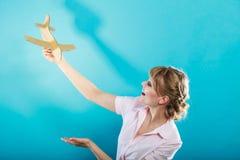 Η γυναίκα που σκέφτεται για τις διακοπές κρατά το αεροπλάνο Στοκ φωτογραφίες με δικαίωμα ελεύθερης χρήσης