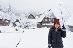 Η γυναίκα που στέκεται και που κρατά τη διαφανή ομπρέλα το χειμώνα και το χιόνι πέφτει με το υπόβαθρο του χιονισμένου χωριού στοκ εικόνα
