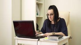 Η γυναίκα που φορά τα γυαλιά κοιτάζει στο όργανο ελέγχου του υπολογιστή κατά τη διάρκεια της εργάσιμης ημέρας απόθεμα βίντεο