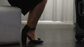 Η γυναίκα που φορά τα παπούτσια στα υψηλά τακούνια που παίρνουν το ταξίδι τοποθετεί σε σάκκο και που περπατούν έξω, ταξίδι απόθεμα βίντεο