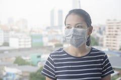 Η γυναίκα που φορά τη μάσκα προσώπου N95 λόγω της ατμοσφαιρικής ρύπανσης στην πόλη έχει τα μοριακά θέματα ή τον ΠΡΩΘΥΠΟΥΡΓΌ 2 5 μ στοκ εικόνα
