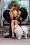 Η γυναίκα που φορά το μαύρο κοστούμι φτερών αγγέλου περιμένει την παρέλαση αποκριών Στοκ Εικόνα