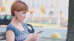 Η γυναίκα που χρησιμοποιεί Smartphone χαλαρώνει στον πάγκο τ την οδό ΣΕ ΑΡΓΗ ΚΊΝΗΣΗ, 4K Νέα χιλιετής γυναίκα στην παραγωγή δενδρο απόθεμα βίντεο
