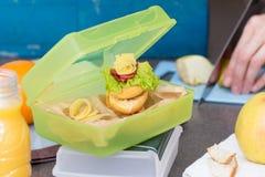 Η γυναίκα προετοιμάζει το μεσημεριανό γεύμα και το βάζει στο κιβώτιο τροφίμων Στοκ Φωτογραφία