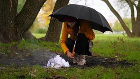 Η γυναίκα προσπαθεί να κάνει την πυρκαγιά κάτω από τη βροχή στο θυελλώδες πάρκο φθινοπώρου φιλμ μικρού μήκους