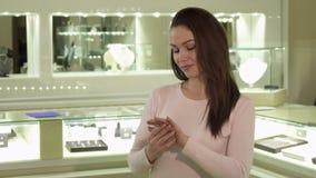 Η γυναίκα προσπαθεί στο δαχτυλίδι στη μπουτίκ κοσμήματος φιλμ μικρού μήκους