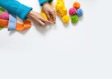 Η γυναίκα πλέκει ένα χρωματισμένο γάντζος ύφασμα επάνω από την όψη Στοκ Εικόνες