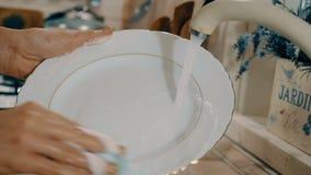 Η γυναίκα πλένει ένα πιάτο με το σαπούνι στην κουζίνα Άποψη κινηματογραφήσεων σε πρώτο πλάνο με τη δευτερεύουσα κίνηση καμερών φιλμ μικρού μήκους