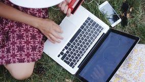 Η γυναίκα πληρώνει για τις αγορές πιστωτικών καρτών μέσω του Διαδικτύου με ένα lap-top απόθεμα βίντεο