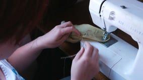 Η γυναίκα ράβει σε μια ράβοντας μηχανή Κινηματογράφηση σε πρώτο πλάνο χεριών απόθεμα βίντεο