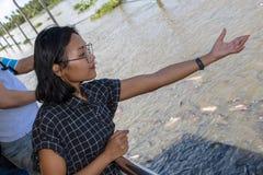 Η γυναίκα ρίχνει το ψωμί για τα ψάρια στον ποταμό στοκ φωτογραφία με δικαίωμα ελεύθερης χρήσης
