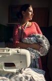 Η γυναίκα ραφτών κοιτάζει στο παράθυρο με την εργασία στα χέρια Στοκ Εικόνες