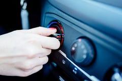 Η γυναίκα ρυθμίζει τη θέρμανση στο αυτοκίνητό της στοκ φωτογραφίες