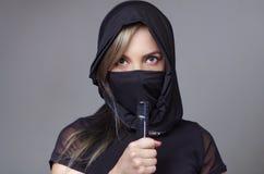 Η γυναίκα Σαμουράι έντυσε στο Μαύρο με το ταίριασμα του πέπλου που καλύπτει το πρόσωπο, που κρατά το χέρι στο ξίφος που αντιμετωπ Στοκ φωτογραφία με δικαίωμα ελεύθερης χρήσης