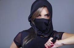 Η γυναίκα Σαμουράι έντυσε στο Μαύρο με το ταίριασμα του πέπλου που καλύπτει το πρόσωπο, που κρατά το χέρι στο ξίφος που αντιμετωπ Στοκ εικόνες με δικαίωμα ελεύθερης χρήσης
