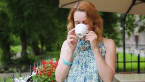 Η γυναίκα σε έναν θερινό καφέ πίνει τη στάση κινηματογραφήσεων σε πρώτο πλάνο τσαγιού Η γυναίκα στέκεται στο υπόβαθρο του πάρκου  απόθεμα βίντεο