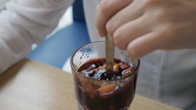 Η γυναίκα σε έναν καφέ ανακατώνει το θερμαμένο κρασί απόθεμα βίντεο