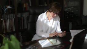 Η γυναίκα σε ένα άσπρο πουκάμισο παίρνει, εξετάζει το τηλέφωνο, αγγίζει απόθεμα βίντεο