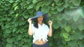 Η γυναίκα σε ένα καπέλο φλερτάρει στο πάρκο απόθεμα βίντεο