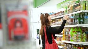 Η γυναίκα σε ένα κατάστημα που διαβάζει μια ετικέτα και αγοράζει τη λεμονάδα φιλμ μικρού μήκους