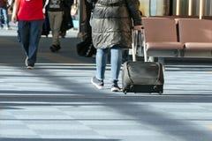 Η γυναίκα σε ένα μαύρες σακάκι και μια βαλίτσα περπατά μεταξύ άλλων ανθρώπων γύρω από την περιμένοντας περιοχή αερολιμένων για να Στοκ εικόνες με δικαίωμα ελεύθερης χρήσης