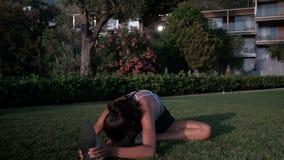 Η γυναίκα σε ένα πάρκο στη χλόη τεντώνει τα πόδια της κατά τη διάρκεια της ικανότητας απόθεμα βίντεο