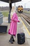 Η γυναίκα σε ένα ρόδινο αδιάβροχο στο σιδηροδρομικό σταθμό Στοκ εικόνες με δικαίωμα ελεύθερης χρήσης