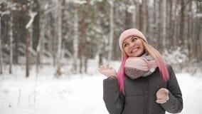 Η γυναίκα σε ένα σακάκι και ένα καπέλο σε σε αργή κίνηση εξετάζει το χιόνι και πιάνει snowflakes το χαμόγελο απόθεμα βίντεο