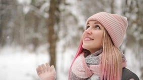 Η γυναίκα σε ένα σακάκι και ένα καπέλο σε σε αργή κίνηση εξετάζει το χιόνι και πιάνει snowflakes το χαμόγελο φιλμ μικρού μήκους