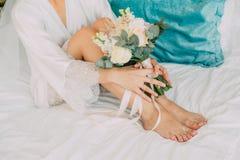 Η γυναίκα σε μια άσπρη τήβεννο κάθεται τα κακά πόδια λουλουδιών Στοκ Φωτογραφίες