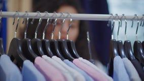 Η γυναίκα σε μια λεωφόρο αγορών επιλέγει τα ενδύματα απόθεμα βίντεο