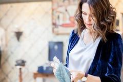 Η γυναίκα σε μια μπλε ζακέτα μετρά τα χρήματα Στοκ φωτογραφία με δικαίωμα ελεύθερης χρήσης