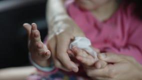 Η γυναίκα σκουπίζει με ένα υγρό χέρι υφασμάτων στο παιδί σας φιλμ μικρού μήκους