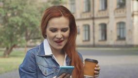 Η γυναίκα σπουδαστής γελά σε αυτό που βλέπει στο smartphone της στην πανεπιστημιούπολη απόθεμα βίντεο