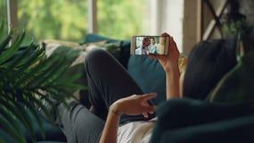 Η γυναίκα σπουδαστής μιλά σε απευθείας σύνδεση κάνοντας τηλεοπτική κλήση ζευγών φίλων στην όμορφη με το smartphone εξετάζοντας τη απόθεμα βίντεο