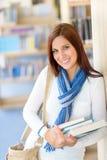 Η γυναίκα σπουδαστής φέρνει τα βιβλία εκπαίδευσης από τη βιβλιοθήκη Στοκ Εικόνα