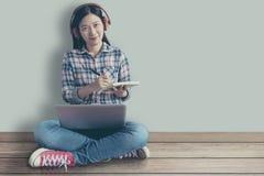 Η γυναίκα σπουδαστής χαλάρωσε τη συνεδρίαση σε ένα ξύλινο πάτωμα στο σπίτι και σειρά μαθημάτων κατάρτισης προσοχής τη σε απευθεία στοκ εικόνα