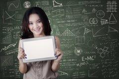 Η γυναίκα σπουδαστής παρουσιάζει κενή οθόνη ταμπλετών στοκ εικόνα
